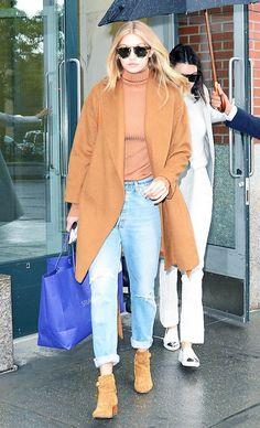 Gigi Hadid wears a turtleneck, camel coat, boyfriend jeans, and suede Saint Laurent boots