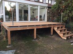 Erhöhte Terrasse aus Bangkirai mit Holztreppe und Außentreppe