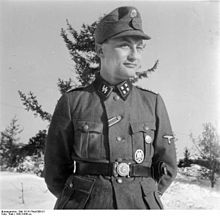 """Gunter d'Alquen (German pronunciation: [ˈdalkən]) (October 24, 1910 - May 15, 1998) was Chief Editor of the SS weekly, Das Schwarze Korps (""""The Black Corps"""") the official newspaper of the Schutzstaffel (SS), and commander of the SS-Standarte Kurt Eggers (SS-Standarte Kurt Eggers. The honour title Kurt Eggers referred to the SS War Correspondent and editor of the SS Magazine Das Schwarze Korps, killed in 1943)."""