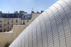 The Pathe Foundation, which promotes cinematography and the heritage of Pathe, has recently added a new public space to their offices in Paris, France. Designed by the Renzo Piano Building Workshop, the modern space is surrounded by historic buildings. The domed roof is made of glass panels that look akin to scales on a snake. These allow the upper rooms to capture plenty of natural sunlight by day and will then emit a faint glow at when lit from within at night.  architecture, design