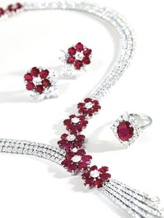 Ruby and Diamond Necklace and Pair of Matching Earrings. The necklace designed as a three-row circular-cut diamond band, to the front embellished with oval-cut ruby and circular-cut diamond flowerheads cascading five diamond-set tassels, completed by a similarly-set flowerhead clasp; and pair of matching earrings; the rubies and diamonds altogether weighing approximately 36.00 and 36.50 carats respectively, mounted in 18 karat white gold.