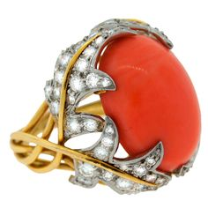 Stunning colorful cocktail ring created by David Webb in the 1970's. Features an oval coral accented with diamonds set in platinum and yellow gold.