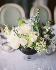 Petite Centerpiece~  Tiny glass vessels helped arrangements of astrantia, white scilla, delphinium, parrot tulips, peonies, stock, rose, viburnum, thlaspi, and larkspur look lush and dramatic.