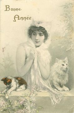 Lisette stands behind wall clasping her furry cape with both hands, two cats on wall, lilac around