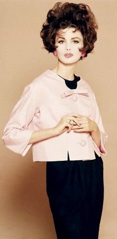 1961. Wearing a pink grainy silk jacket by Mainbocher, over a black dress, Image by © Condé Nast Archive/CORBIS