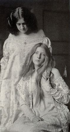 Sisters -  the seated girl is either deceased or near death with illness. The standing sister is holding her hand up, not holding hands with her.