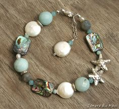 This fun mermaid bracelet features a playful mix of aqua amazonite, paua abalone shell, white coin pearls, labradorite, swarovski crystals Hill Tribe fine silver starfish and accent beads. Hill Tribe silver is pure accept for the solder need to connect the piece together if any. This beachy summer bracelet has cool ocean hues and would look great with your summer outfit. Wire wrapping is sterling silver. Clasp, chain and findings are sterling silver  Bracelet size is adjustable from 6 1/2 to…