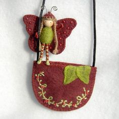 This is a really awesome butterfly pouch necklace. This sweet butterfly stands 2 1/2 inches tall and has wool felt wings in a beautiful dark berry