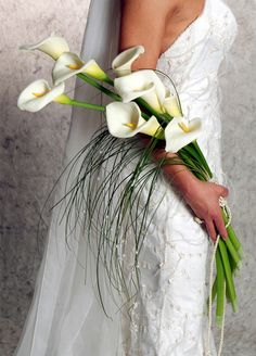 Wow! A bride who knows how to carry this kind of wedding bouquet! She should bring her arm a bit up and more to the front, somehow like carrying a baby. I guess the posture is for the photo shoot of the bouquet. Great photo, body, dress and bouquet. Great cut and seal of the flower stems. Love these little accents with the simple string and the tiny pearls.