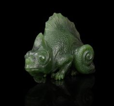 A jewelled hardstone model of a chameleon Fabergé, circa 1900, marked 'Fabergé' in Latin realistically carved in nephrite with diamond-set eyes length: 7.6cm (3in).