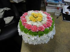B-day cake flower arrangement white, pink,and yellow.