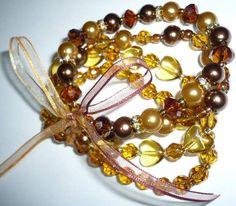 Juego de pulseras en perlas y cristales checos, unidas con cinta de seda. Precio Col$30.000.
