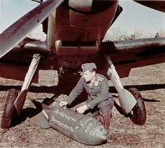 Auxiliar escribiendo dedicatorias en una bomba debajo de un Ju-87