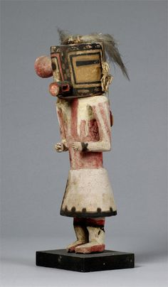 Malo kachina tihu, Hopi. Colton 130 (table 13). [jcx]. Case mask, tube mouth, rectangular eyes, nose a vertical line : a checker board for Malo. Blossom in place of one ear, tuft of hair on other, with feathers.