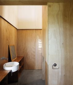 Minimalist doesn't have to mean monochromatic or marble. The Gaboon-plywood walls of the McKenzie residence in New Zealand flow through into the bathroom without a door to get in the way. Photo by Patrick Reynolds.  Photo by: Patrick Reynolds