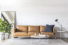 Our Lennon sofa in family-friendly Antico Leather is a great option for a relaxed modern living room.  #tanleathersofa #lennonsofa #brownleathersofa #tanlounge #tanleatherlounge #minimaldesign #australiandesign #cameronfoggo #armadillo&co #mancave #masculineinteriors #moderndesign #australianmade