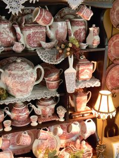 hutch full of red transferware is mixed with some vintage lace and linens