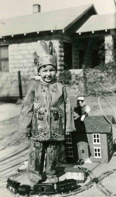 This photograph is of young Jack Riddle in his yard in the Warren area of Bisbee, Arizona with his new train set and costume on Christmas morning in 1930.  This image is from the photograph collection of the Bisbee Mining & Historical Museum
