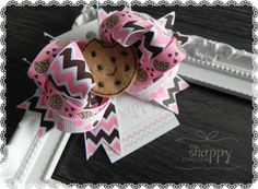 """This elaborate and beautiful hair bow is a ponytail's best friend, and sweetest sidekick! Featuring a smiling felt cookie surrounded by loopy layers of beautiful coordinating pink and brown ribbon, it's easy to picture your little girl's ponytail topped by a bow as beautifu as this! Size: 4.5"""" x 4"""" Materials Used: Grosgrain Ribbon Cotton Thread Silicone Steel Adhesive Felt Â"""