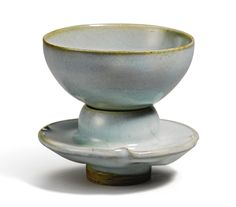 A 'Jun' cup and stand, Song dynasty, the cup with rounded sides resting on a short foot, supported on a cupstand with a hollow bowl with rounded sides collared with a quatrefoil dish with slightly curved sides, all raised on a hollow foot, covered overall in a lavender-blue glaze thinning to a mushroom tone at the rims, Japanese wood box  Quantity: 3.  8.3cm., 3 1/4 in.