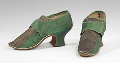 Green silk satin latchet shoes with metallic lace trim, probably British, 1730-1755. The favored trim of a wide band of metallic lace up the center front and often up the center back came into style in the last decades of the 1600s and persisted until around 1750. Also of note is the dog-leg (stepped) side seam, a feature which developed as latchets widened to support increasingly large buckles in first half of the century, and which was retained until about 1770.