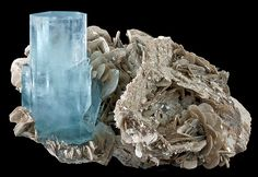 Aquamarine crystal with a Muscovite  From Nagar, Hunza Valley, Gilgit-Baltistan, Pakistan.  Measures 9.1 cm by 14.6 cm by 10 cm in total size.  Ex. Herbert Obodda Mineral Collection No. 1065