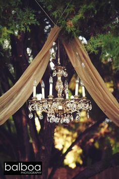 Pretty vintage chandelier with burlap fabric drape for a lovely wedding ceremony backdrop