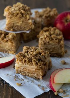 Sliced Apple Crisp Bars with layers of cinnamon, sugar, apples and a crunchy oat topping. Layered on parchment paper with apple slices and crumble bits.
