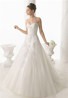 Nectar is a timeless style with its fitted sweetheart bodice and full princess skirt of beaded lace and tulle. Nectar is paired here with a lace bridal jacket with a portrait neckline and short sleeves.