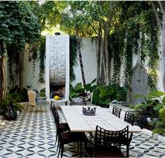 Patterned Tile for the Floor in the Patio of Open Dining Area with Stone Accents Fireplace and Greenery Surrounds
