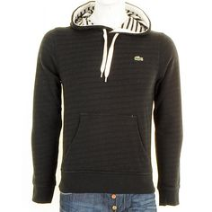 Lacoste Live Hooded Jumper In Black, Ultra Slim Fit. Draw string hood with a chunky white drawstring and a cream trim as well as a striped chain fleece interior in black and cream. One large pouch pocket on the waist. The interior of this jumper is striped chained fleece which gives the jumper a faint striped appearance. Stretch rib cuffs on the long sleeves and waistband. The signature Lacoste Live Crocodile logo is on the left of the chest. 100% Cotton.