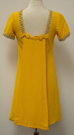 Vintage 1960's MOD A-Line Mini Dress Canary Yellow Crepe with Lame & Rhinestone Trim and Train   This MOD 1960's Vintage Cocktail Dress has an A-Line silhouette that drops free from the shoulders. Trimmed in silver and gold tinsel cord embedded with rhinestones and with a short train that falls from the square scoop back and embellished with bows
