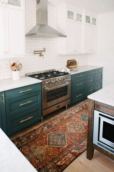 Love the teal colored lower cabinets and the beautiful Persian rug that adds just the right accent...