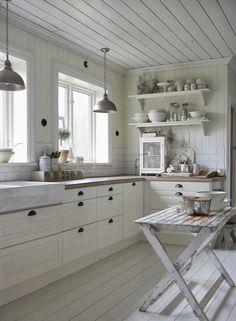 Biała kuchnia z drewnianym rustykalnym stołem