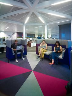 Carpet tiles can provide dimension and depth to standard office spaces through various floor designs. As a result, these floor designs give the spaces a modern look like this bold geometric / pinwheel floor design featuring pink, purple and white carpet tiles.