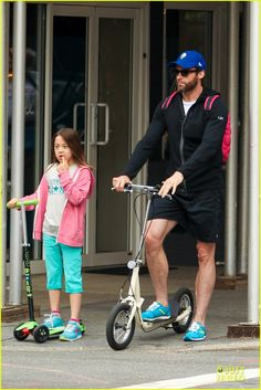 Hugh Jackman rides his scooter while taking his daughter to school on June 10, 2013