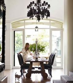 Homeowner Talitha Becker, with Burmese kitten Smokey, sets the table in the dining area. Chandelier bought while on a trip in Europe. Table from Temple Door