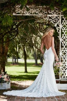 This designer sheath wedding gown from Martina Liana features graphic lace over ivory Imperial crepe. Its sweetheart neckline is accented with sexy spaghetti straps. The back zips up under pearl buttons and flows perfectly into a sleek chapel train. Style 794 by @martinaliana.