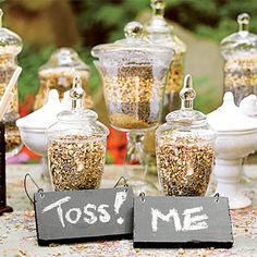 """Shredded herbs to be showered on the newlyweds after the ceremony greet guests in glass vessels at a """"Toss Me"""" table.   guests are offered aromatic bits of lavender, jasmine and chamomile to toss as they recessed down the aisle."""