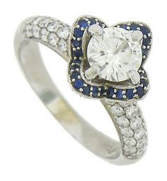This spectacular floral inspired engagement ring is fashioned as a blooming rose. Diamond frosted petals are tipped in deep blue sapphires and open to present a dazzling .82 carat, H color, Si1 clarity diamond. Additional round cut diamonds are pressed into the rings shoulders. This antique style ring is fashioned of 14K white gold and measures 5.47 mm in width. Size 7. We can re-size slightly.