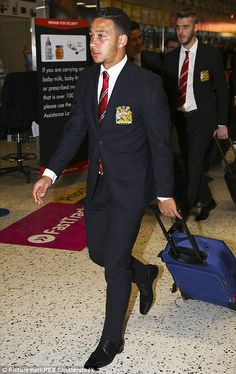 Memphis Depay wheels his luggage through Manchester Airport
