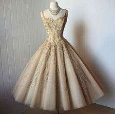 Vintage 1950s dress   ...the most exquisite beaded nude tulle dress with a boned corset bodice and a full circle skirt  For more fashion and wedding inspiration visit www.finditforweddings.com Retro