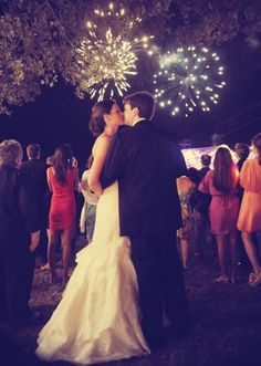 The bride and groom steal a kiss during fireworks