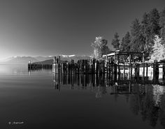 Schweitzer Ski Resort from the Boatworks Marina at Sunnyside Point on Lake Pend Oreille. This shows a dusting of snow on the runs in early November of 2010. Also Fall colors and pilings are reflected. Located near Sandpoint, Idaho. Photo 3 in a series of both color and black and white.