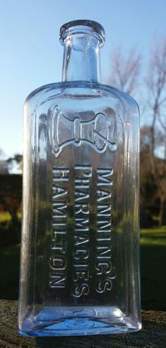 Manning's Pharmacies Hamilton with pictorial mortar and pestle. Very rare in light electric blue glass 16.5cm.