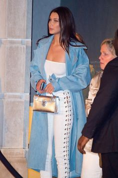 Bella Hadid Wore Lace-Up Jeans, and Guess Which Supermodel's Got Them Too? Bella Hadid Wearing White Lace-Up Jeans Bella styled her denim with a white tube top, Rask NYC oversize trench, heeled sandals, and a metallic mini bag.