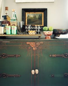 A tray of bar essentials atop a green cabinet