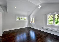Dormer Window Captures Sunlight And Ephasizes High Ceilings Grey Walls White Trim Light Gray