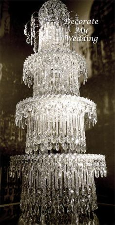The Crystal Wedding Cake Centerpiece   Maxine - Rhinestone Strands & Teardrops   4 Tier   This Crystal Wedding Cake Centerpiece is truly a sensational showpiece.  Adorned with thousands of sparkling crystal rhinestone strands and teardrops. Each tier rises above the one below it displaying thousands of crystals that reflect in the mirror on which each tier stands.  This crystal wedding cake is an original design that will take your crystal wedding decorations to the next level.