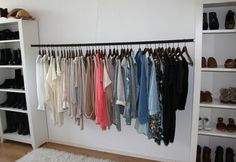 i love this idea of hanging a pole between two shelves! Also a shelf unit or armoire in the middle with poles on either side